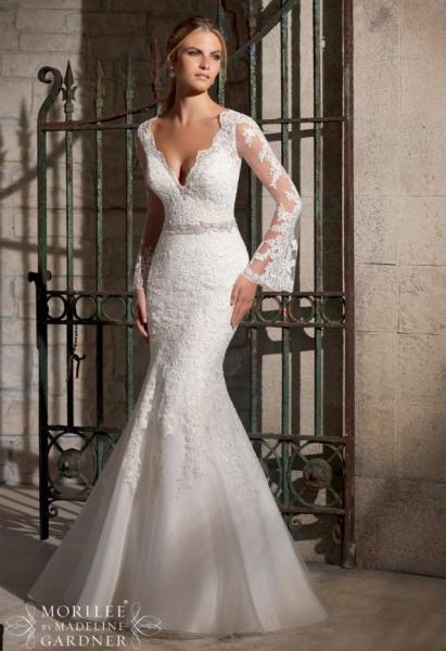 [Image: Having a fall or winter wedding? This classic white wedding dress with lace sleeves and mermaid style bottom is popular among fall brides. ]